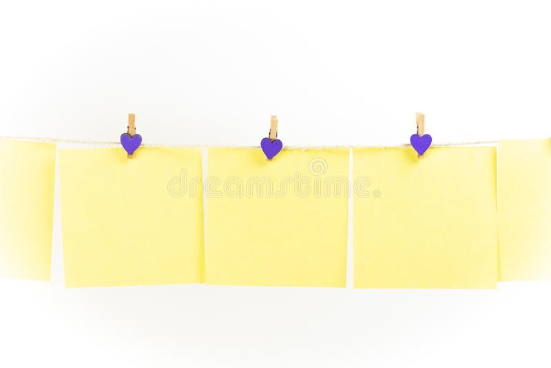 在晒衣绳的黄色贴纸与在白色背景隔绝的晒衣夹 免版税库存照片
