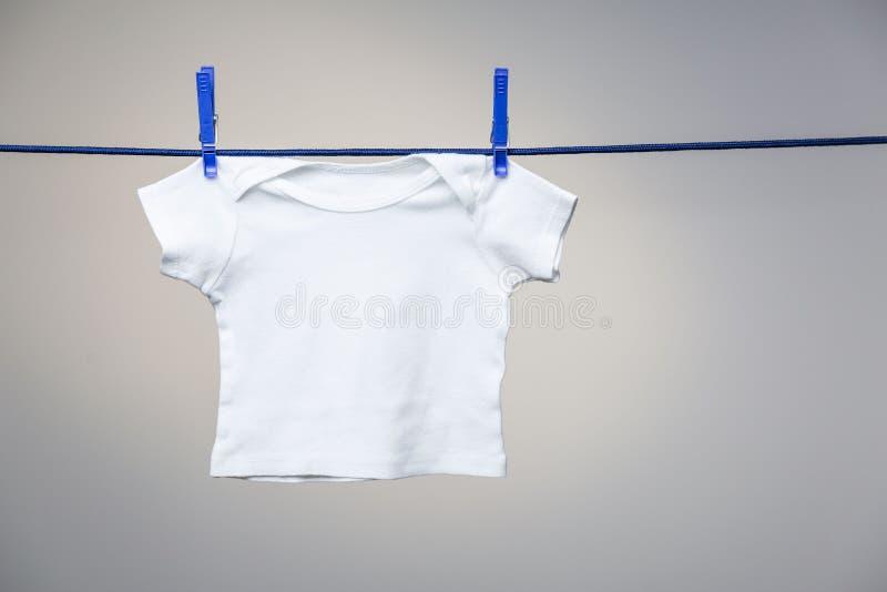 在晒衣绳的婴孩衬衣 免版税库存图片