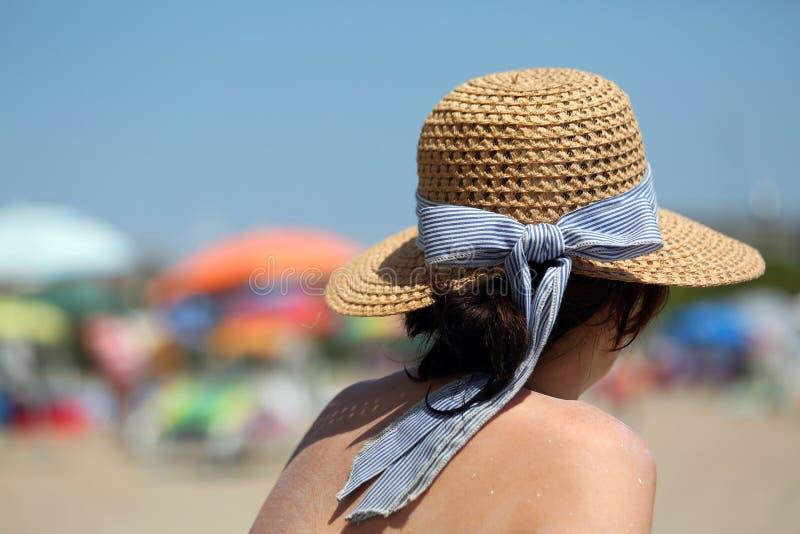 在晒黑的富有的妇女与在游人海滩的草帽期间  图库摄影