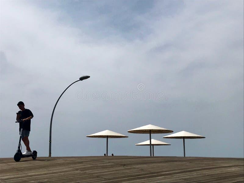 在晒黑的黄沙的时髦的懒人sunbed在海滩 库存图片