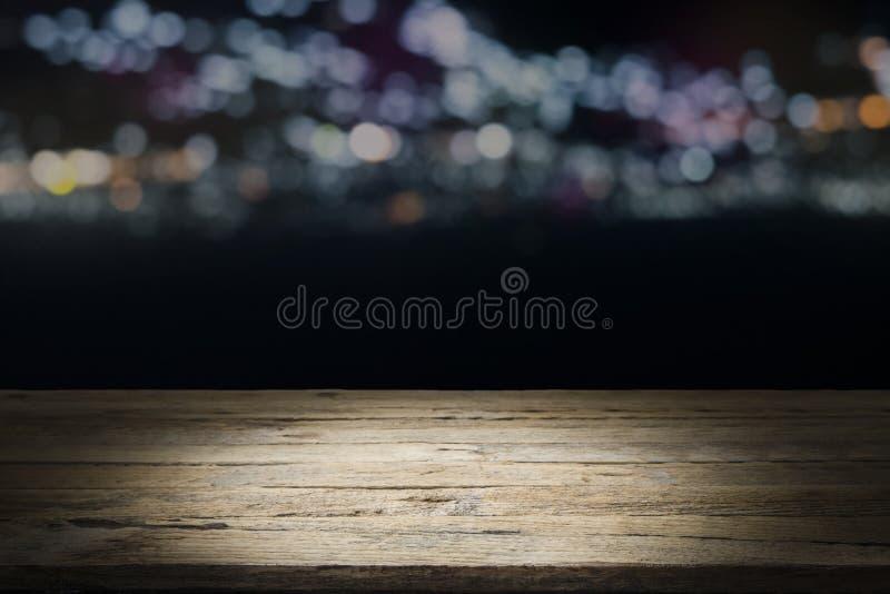 在晚上倒空木桌平台和bokeh 库存图片