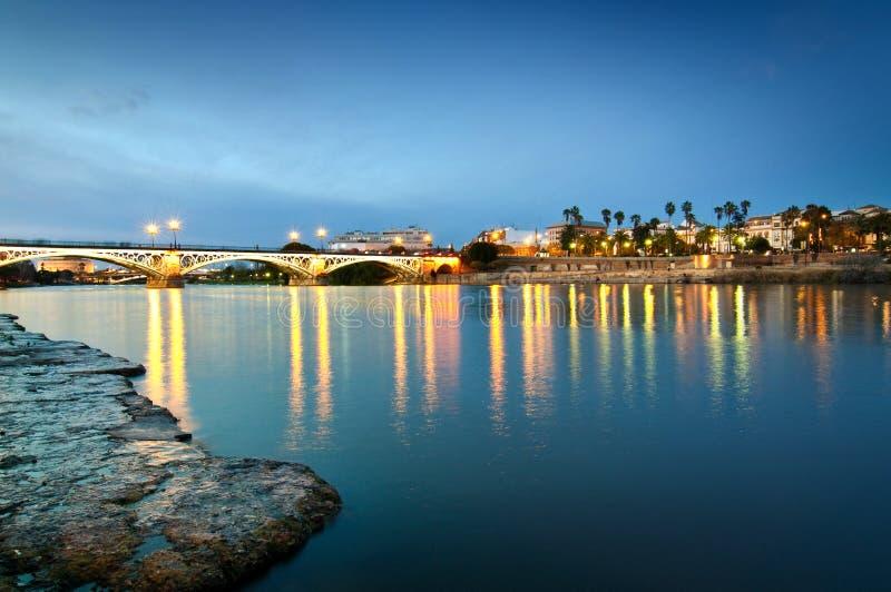 在晚上光的Triana桥梁,塞维利亚西班牙 免版税库存照片