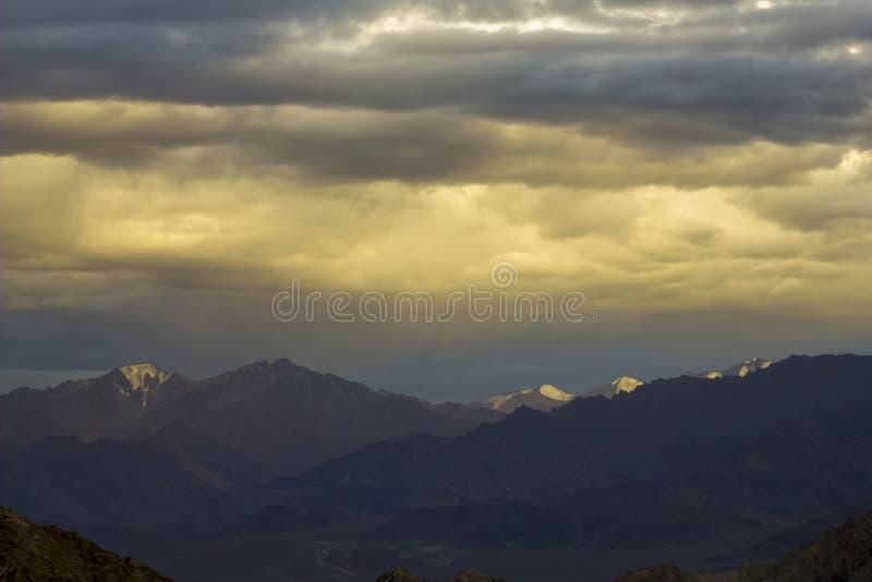 在晚上天空的阳光在多雪的山 库存照片