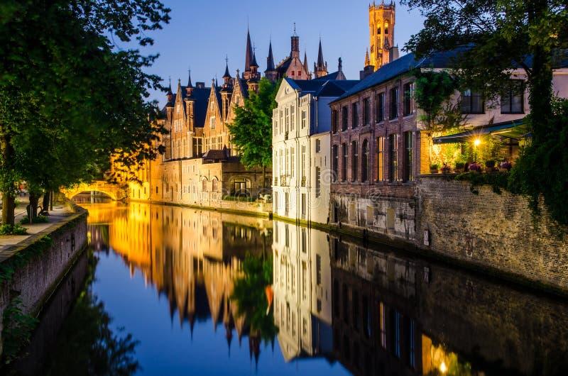在晚上浇灌运河、中世纪房子和钟楼在布鲁日 免版税库存照片