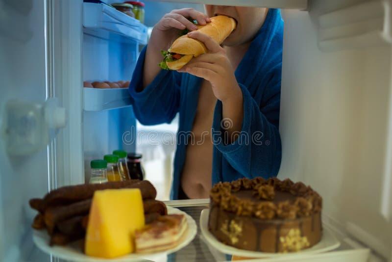 在晚上肥头大耳的人违犯饮食 免版税库存图片