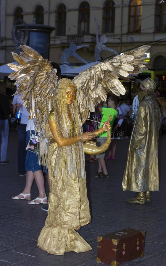 在晚上街道的金黄活天使雕象 形式天使的女孩 库存照片