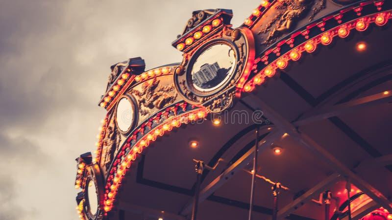 在晚上被照亮的旋转木马转盘 反对平衡天空的反射都市风景在夏天 节日幸福时光想法 库存图片