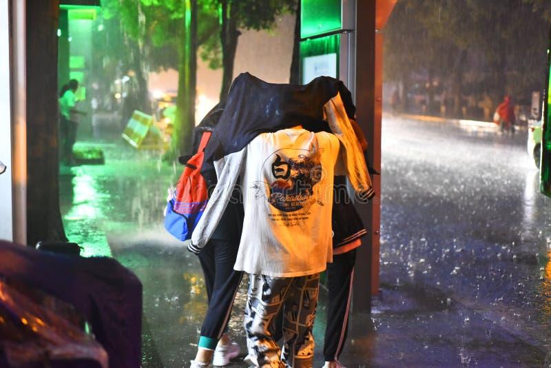 在晚上,一场突然的暴雨,三名中学学生在雨中使用他们的上面阻拦他们的头并且走了 免版税库存图片