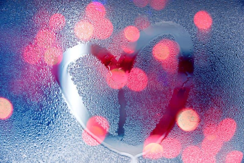 在晚上,凹道在湿玻璃的心脏形状下雨与光 免版税库存照片