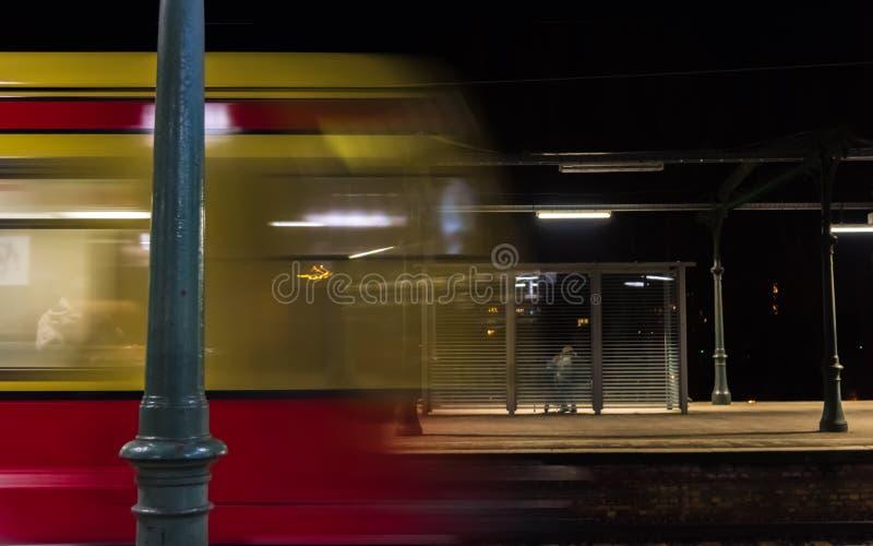 在晚上,当黄色红色火车到达时 图库摄影