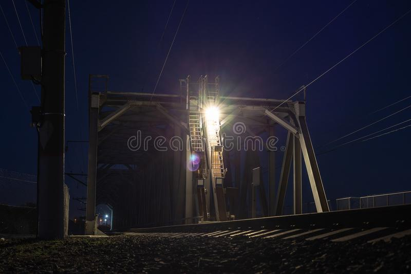 在晚上,运输建筑铺铁路在河的桥梁 免版税库存图片