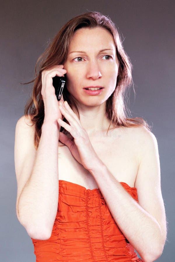 在晚礼服的担心的妇女电话优等的美丽的年轻人 免版税图库摄影