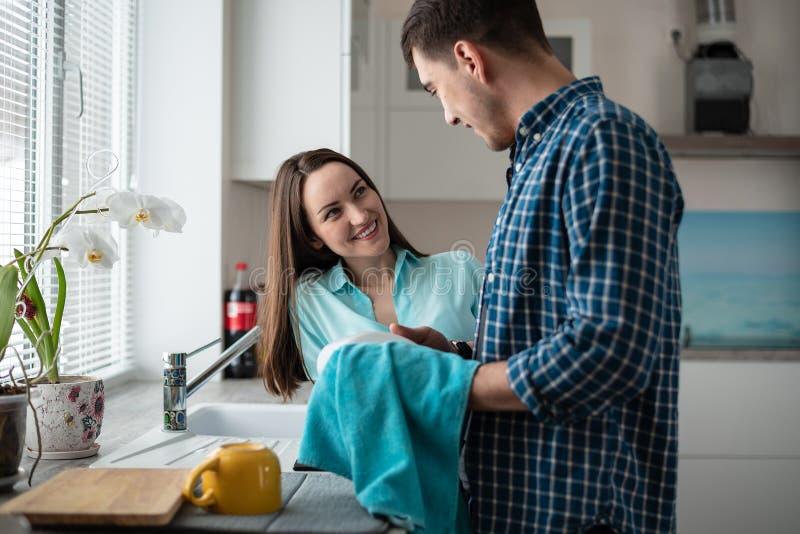 在晚餐,愉快的家庭生活以后一起结合洗涤的盘 免版税图库摄影