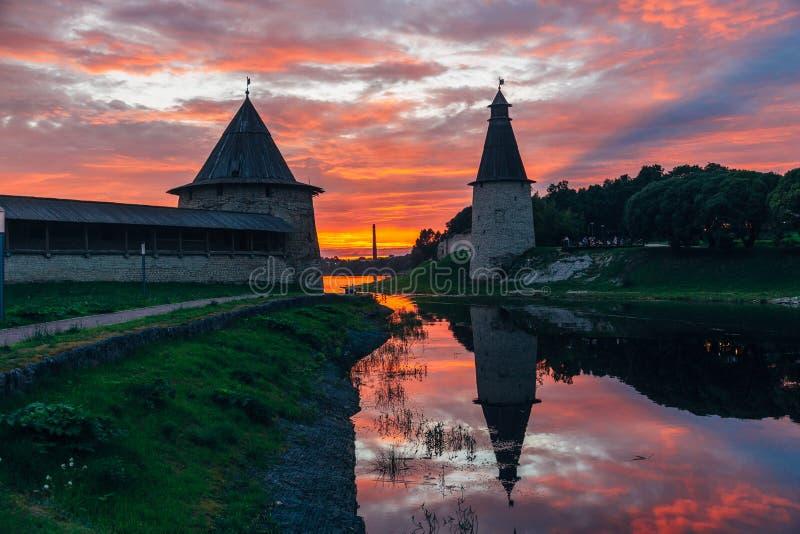 在普斯克夫堡垒手表塔上的绯红色日落 免版税库存照片