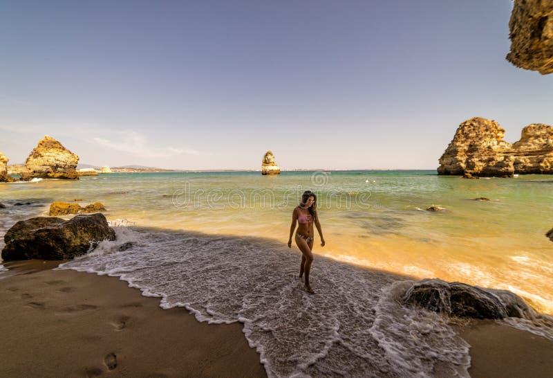 在普腊亚的妇女旅游姿势做卡米洛海滩拉各斯,葡萄牙 阿尔加威地区 免版税库存照片