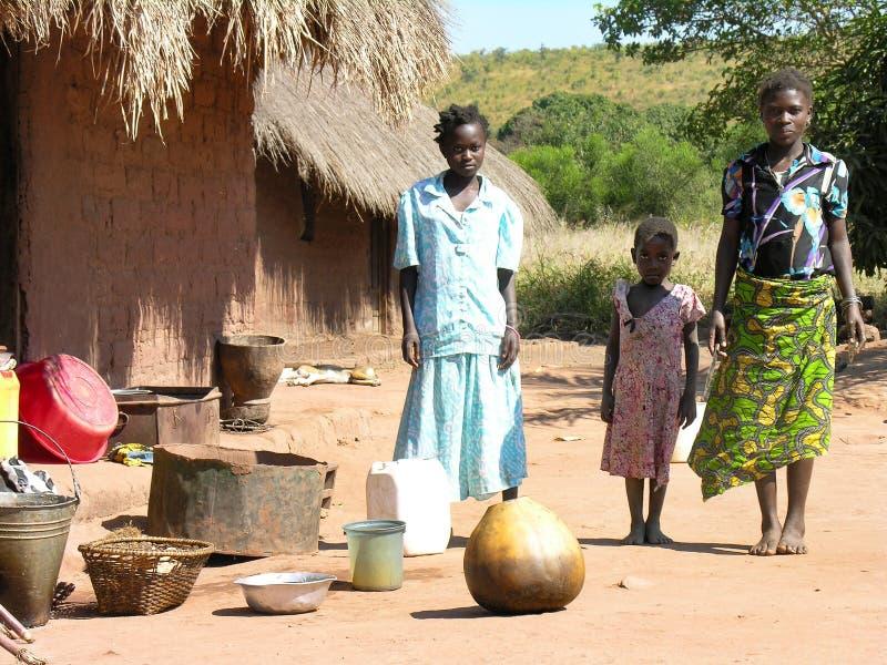 在普韦托附近,加丹加高原,刚果民主共和国:摆在他们的小屋前面的母亲和女儿 库存图片