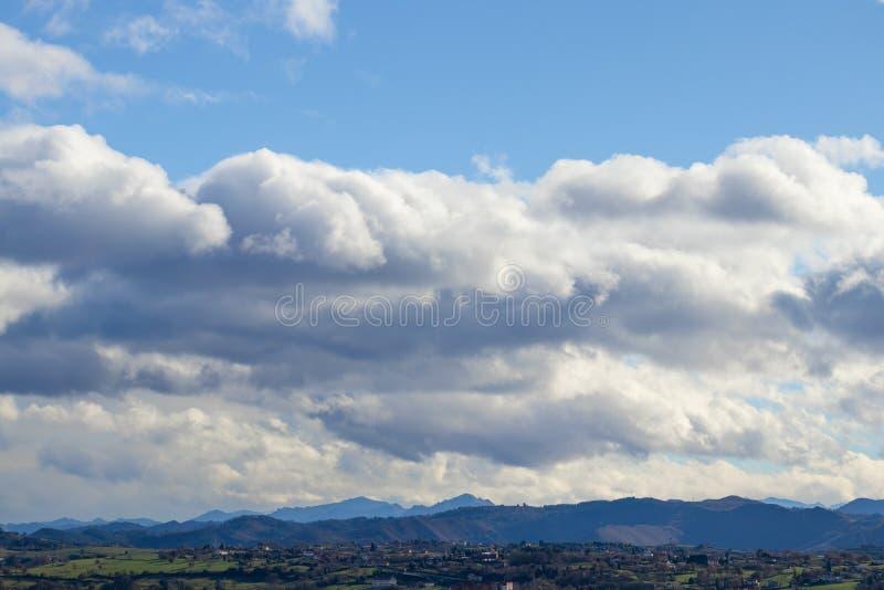 在晴天的山脉在雨前的对比的雨云 库存照片
