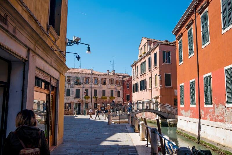 在晴朗的夏日期间与清楚的天空蔚蓝,五颜六色的威尼斯式大厦和胡同看法有水运河和清楚的天空蔚蓝的 库存照片