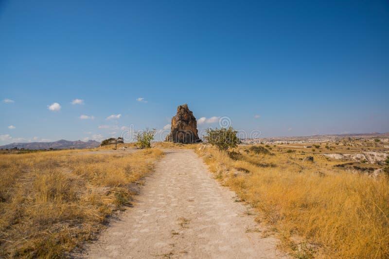 在晴朗的天气的美好的风景 在领域的路,在距离一个异常的岩石 Cappadocia,土耳其 免版税库存图片