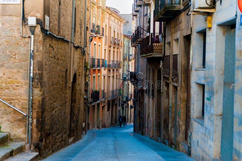 在晴朗的春日期间,人们在小加泰罗尼亚的西班牙中世纪镇街道走  免版税库存照片