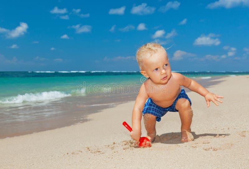 在晴朗的热带海滩的愉快的男婴开掘的沙子 图库摄影
