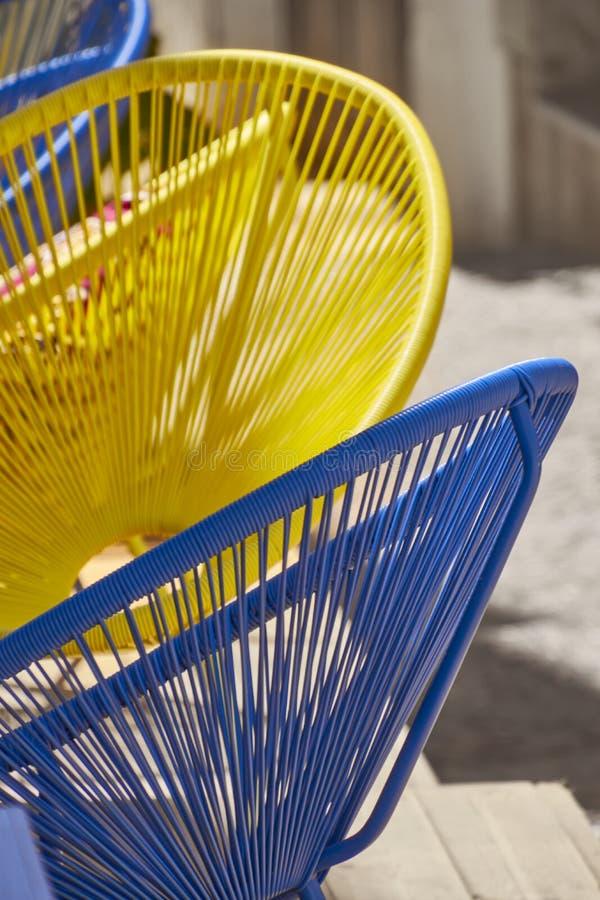 在晴朗的街道的蓝色和黄色椅子 库存照片