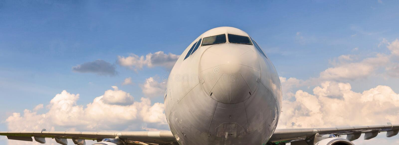 在晴朗的cloudscape全景前面的飞机 免版税库存照片