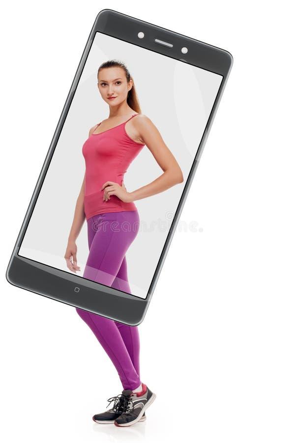 在智能手机后的健身女孩 免版税库存图片