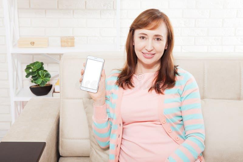 在智能手机屏幕上的空白的白色空间 拿着移动newspaer读取的女实业家 有手机的微笑的可爱的中年妇女 嘲笑 库存照片