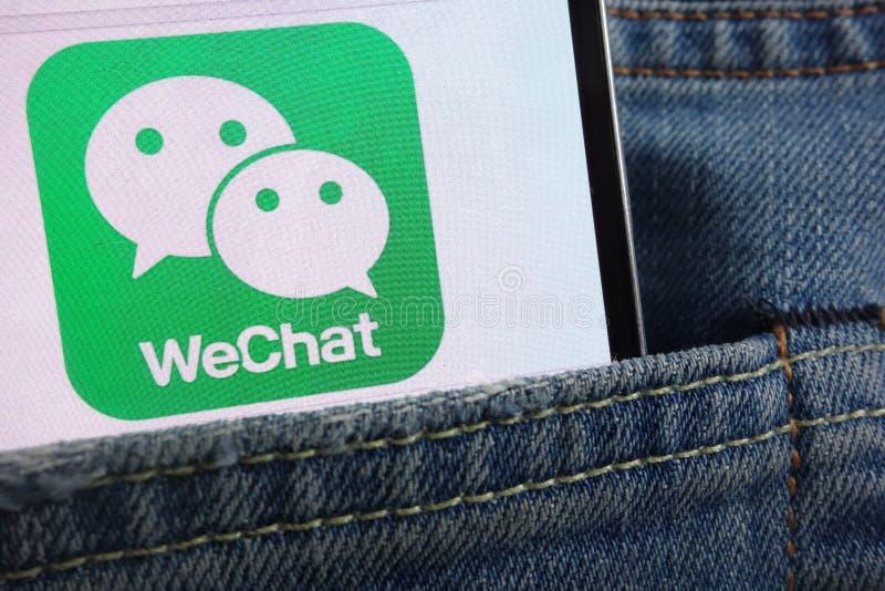 在智能手机显示的微信商标掩藏在牛仔裤装在口袋里 免版税库存图片