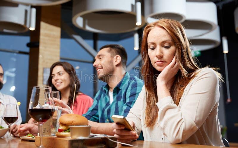 在智能手机的乏味妇女传讯在餐馆 库存照片
