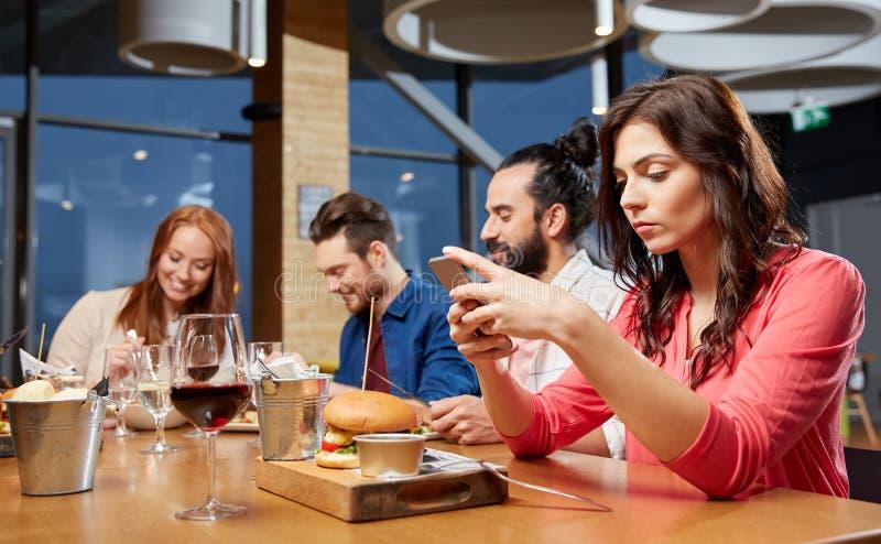 在智能手机的乏味妇女传讯在餐馆 免版税库存图片