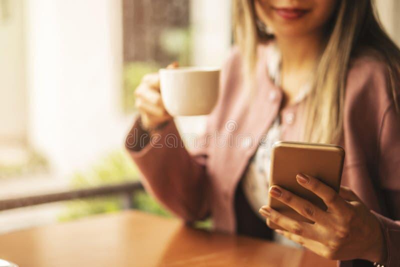 在智能手机的女商人键入的短信在咖啡馆,关闭有屏幕的女性手固定的单元电话 免版税库存照片
