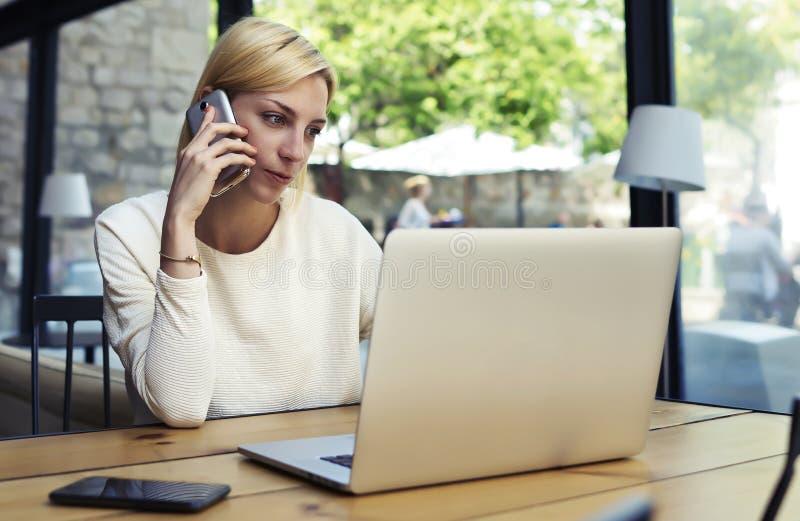 在智能手机的女性谈话,当看网书屏幕时 库存照片
