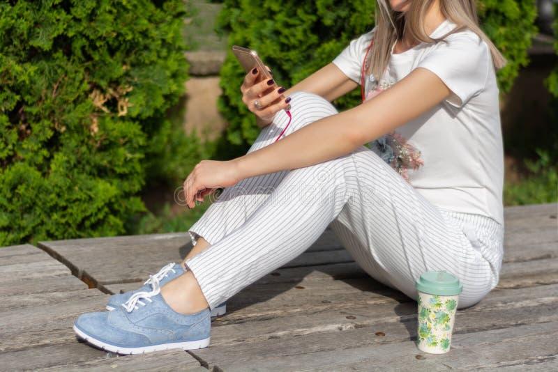 在智能手机的妇女工作和坐在一杯咖啡的长凳旁边在公园在一个晴朗的春日 库存图片