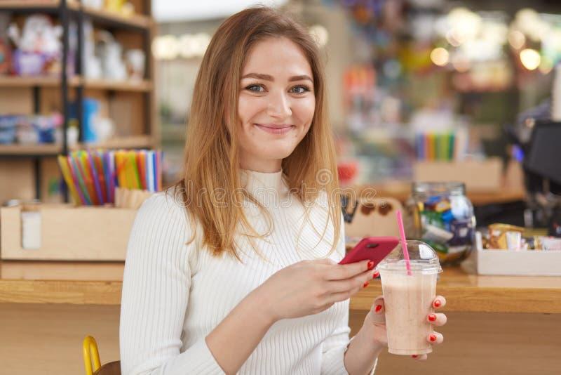 在智能手机的妇女键入的消息现代咖啡馆一会儿享受新牛奶coocktail 年轻俏丽的女孩的图象坐smilling在 库存照片