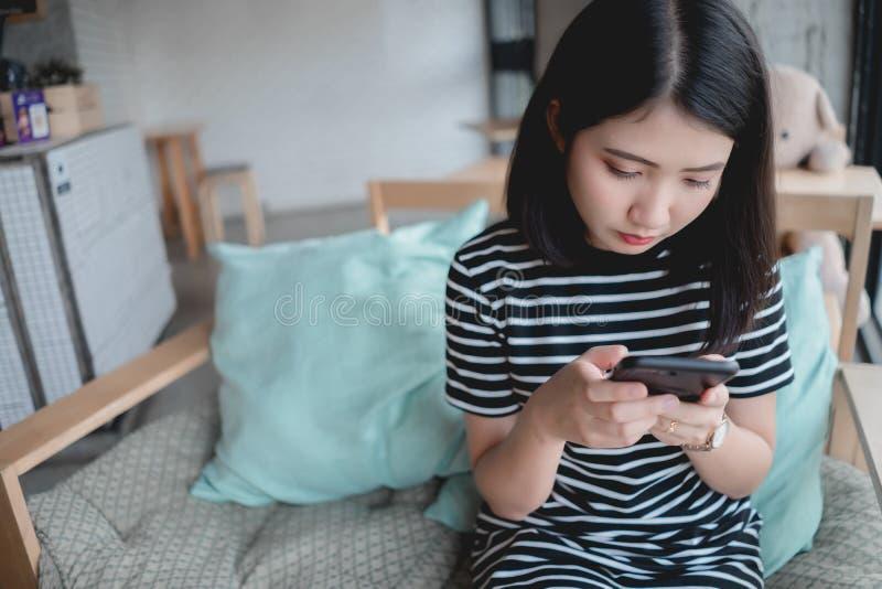 在智能手机的妇女键入的短信在咖啡馆 坐在桌上的年轻亚裔女孩在咖啡馆使用手机 连接数 免版税库存照片