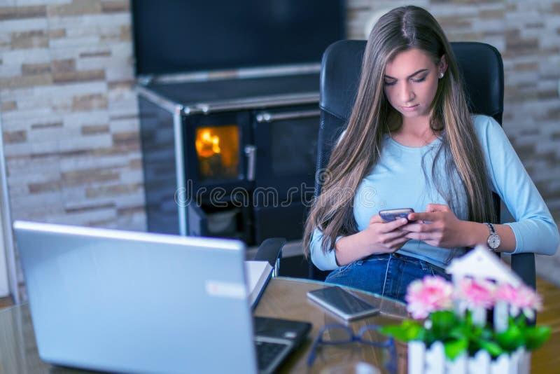 在智能手机的妇女键入的短信,当坐由桌在办公室时 免版税图库摄影