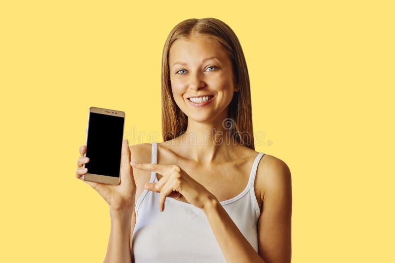在智能手机的愉快的微笑的妇女点,在黄色背景 免版税库存照片