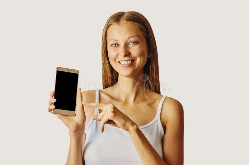 在智能手机的愉快的微笑的妇女点,被隔绝在浅灰色的背景 库存图片