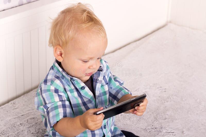 在智能手机的逗人喜爱的男婴观看的动画片 使用与电话的滑稽的小孩 免版税库存照片