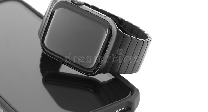 在智能手机的黑巧妙的手表 库存图片