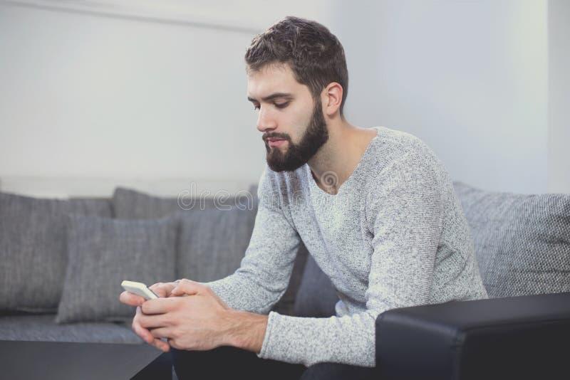 在智能手机的年轻偶然人传讯在沙发 免版税库存图片
