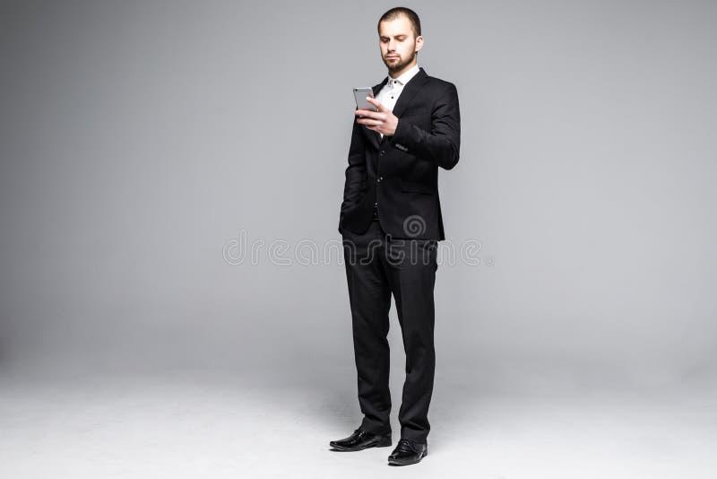 在智能手机触摸屏上的年轻商人键入的消息 充分的体长画象被隔绝在白色演播室背景 免版税库存照片