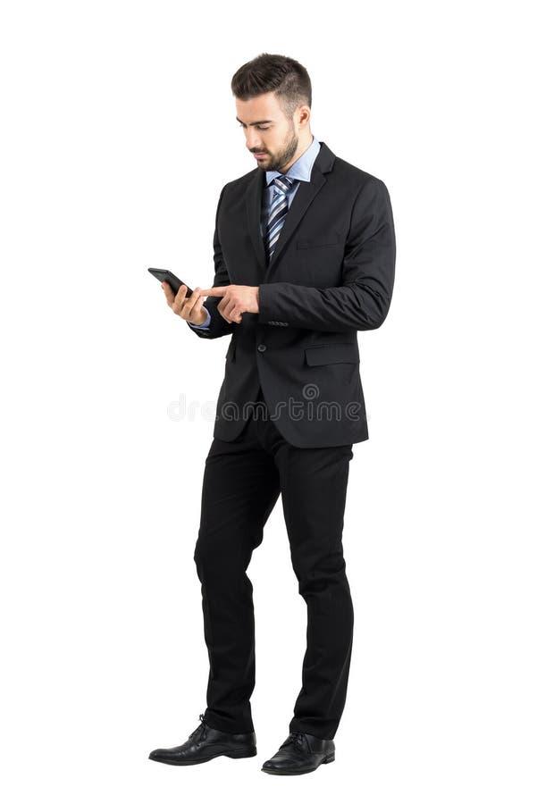 在智能手机触摸屏上的年轻有胡子的商人键入的消息 库存图片