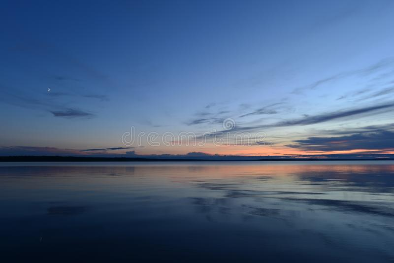 在暮色光的月出在日落的天空蔚蓝在湖的安静的镜子水 免版税库存图片