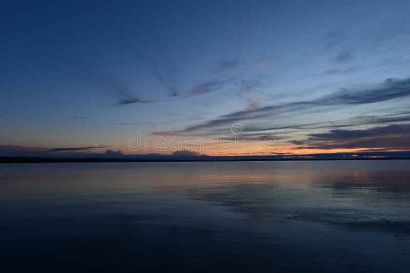 在暮色日落前的光亮的深蓝天空在湖的水的安静的表面被反射 免版税库存图片