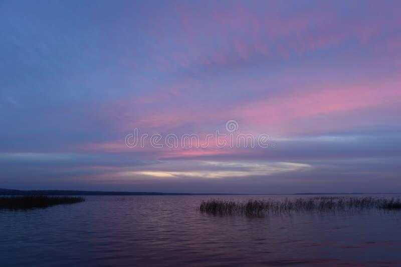在暮色焕发的天空蔚蓝在湖的水上在一个温暖的秋天晚上 免版税库存图片