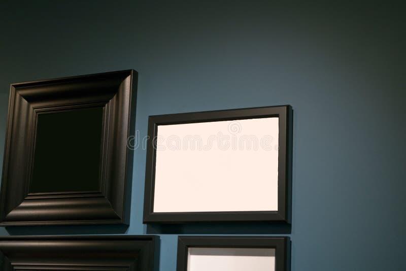 在曝光不足蓝色墙壁上的画框孤立 图库摄影