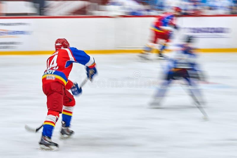 在曲棍球期间,未认出的曲棍球运动员完成 免版税库存照片